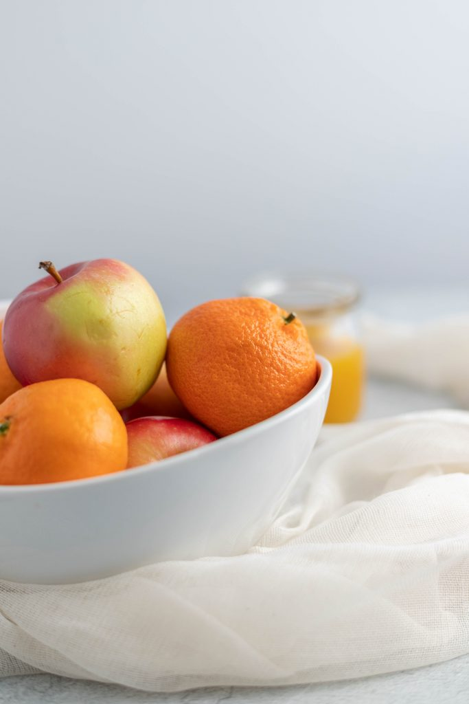 a bowl of oranges and an apple